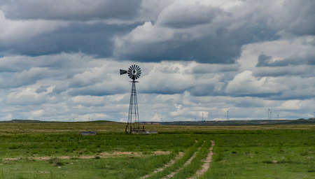 Small old wind turbine in a field against a cloudy sky in Tennessee, USA