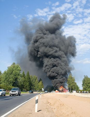 truck in fire with black smoke on the road photo