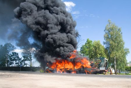 fire damage: truck in fire with black smoke on the road