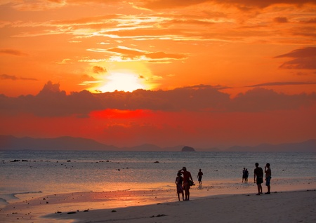 peoples on beach look to sunset photo