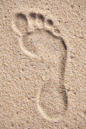 Single footprint on sand beach Stock Photo