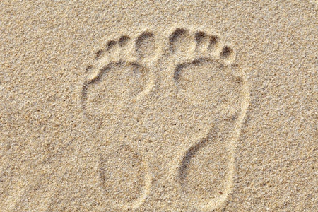 Two Footprints in sand at the Beach