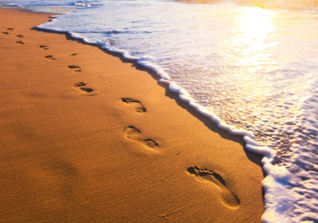 beach feet: beach, wave and footsteps at sunset time
