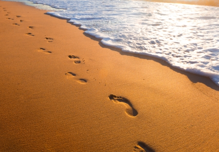 sandy feet: beach, wave and footsteps at sunset time