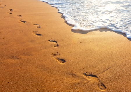 footprint sand: beach, wave and footsteps at sunset time