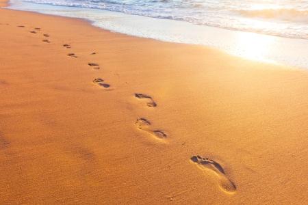 strand, golf en voetstappen bij zonsondergang tijd