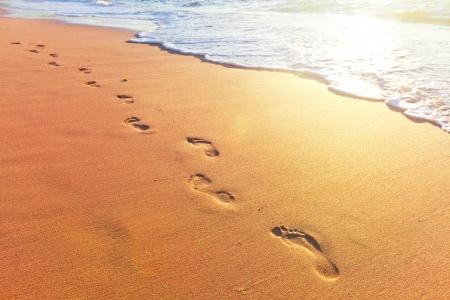 huella pie: playa, las olas y los pasos a la hora de la puesta del sol Foto de archivo