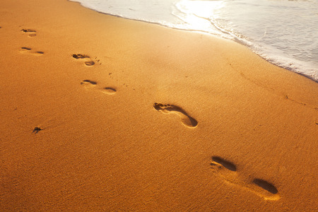 sea mark: beach, wave and footsteps at sunset time