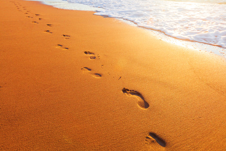 footprint sand: beach, wave and footprints at sunset time