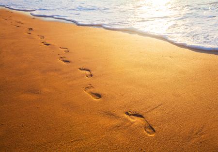 huellas pies: playa, las olas y las huellas en el tiempo de la puesta del sol Foto de archivo