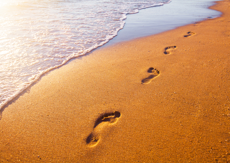 footprints in sand: beach, wave and footprints at sunset time