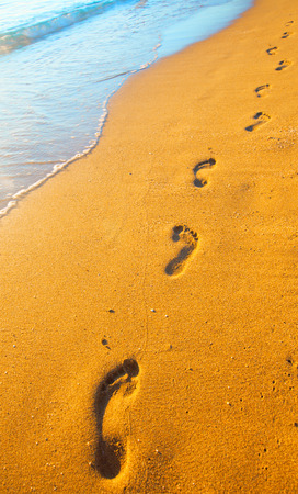 sandy feet: beach, wave and footprints at sunset time