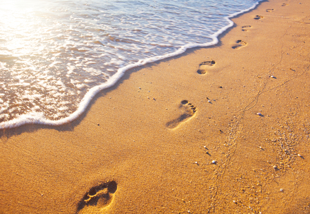 sea mark: beach, wave and footprints at sunset time