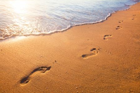 plage, vague et empreintes au moment du coucher du soleil