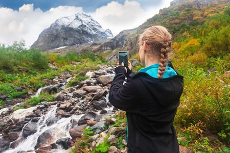 mountin: woman taking a photo of mountin on smartphone Stock Photo