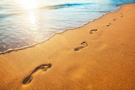 beach, wave and footprints at sunset time Stock Photo - 70104258