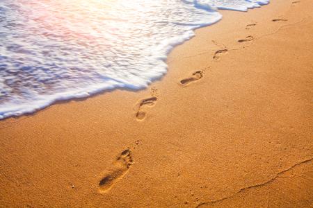 plaża, fala i ślady stóp o zachodzie słońca