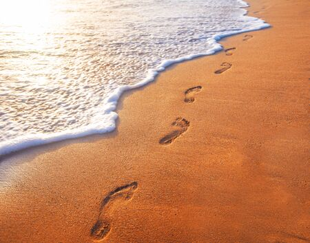 beach, wave and footprints at sunset time Stock Photo