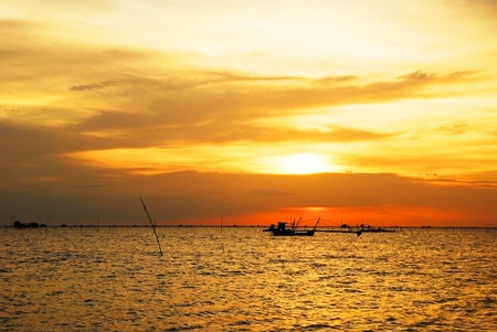 Seascape with fishing boat at sunset  photo