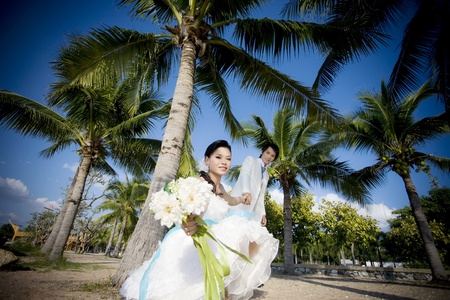 young wedding couple freshly wed groom and bride posing outdoors on their wedding day   photo