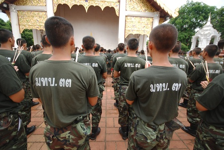 Thai military walk with lighted candles in hand around a temple.