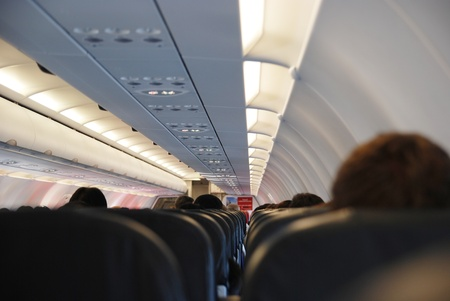 armrest: Airplane seat and window inside an aircraft