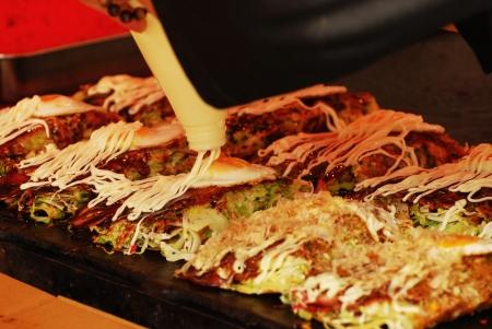 Japanese food cooking Okonomiyaki Squeezing mayonnaise on a Japanese pizza