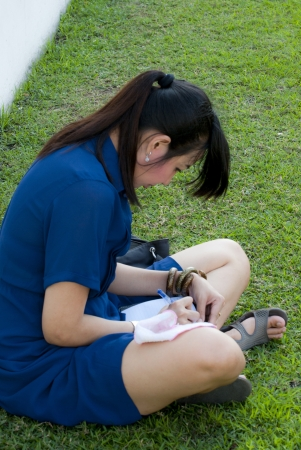 Woman writing on a sheet of paper while sitting  photo