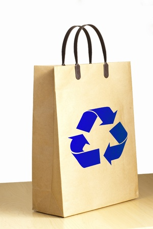 Recycle logo on paper bag on wooden floor against the white wall  photo