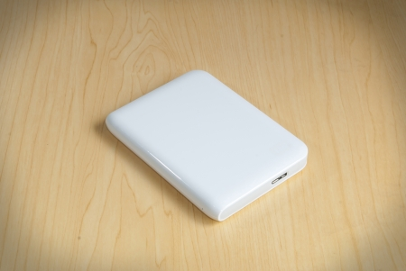 Portable external hard drive white color on the wood