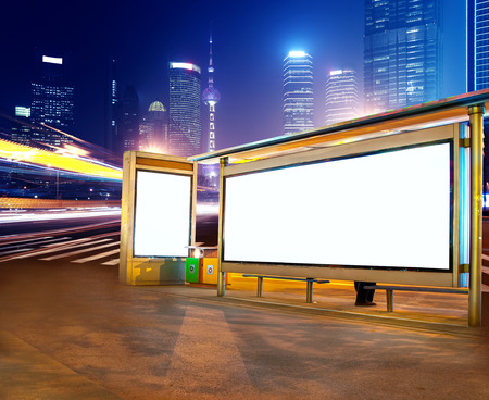 white poster: Road car light trails through at modern city advertising light boxes,in shanghai,China