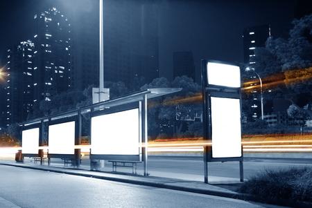 Blank billboard on bus stop at night Imagens