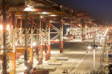 ports are busy loading and unloading containers, at night