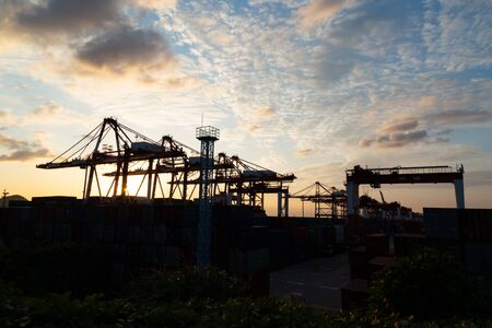 Container terminal against sunset sky.  Large cranes are  working Imagens