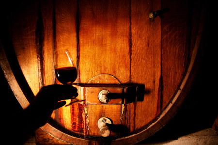Wine maker with red wine tasting in winery featuring wine barrels