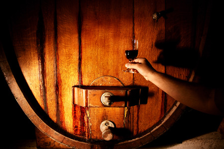 casks: Wine makers tasting in winery featuring wine barrels Stock Photo