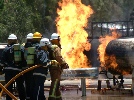 out of control: Gas tank on fire with Emergency Fire Fighters.  Featuring a gas tank burning out of control in a bush fire after an emergency call