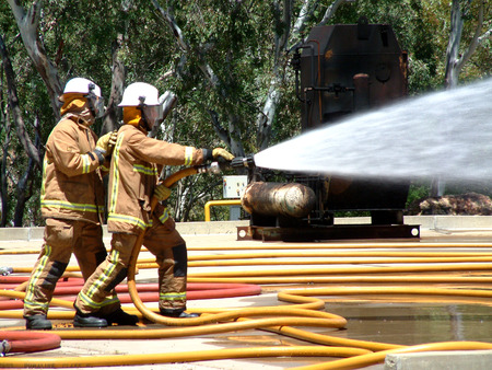 bush fire: Emergency Teams fighting a fire. Featuring a gas tank burning out of control in a bush fire after a 911 - 000 call with fire hose extinguishing. Editorial