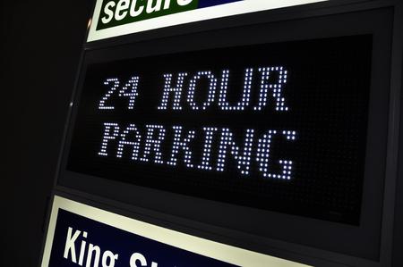 busy city: 24 twenty four hour car parking street sign in a busy city. Under cover car parking