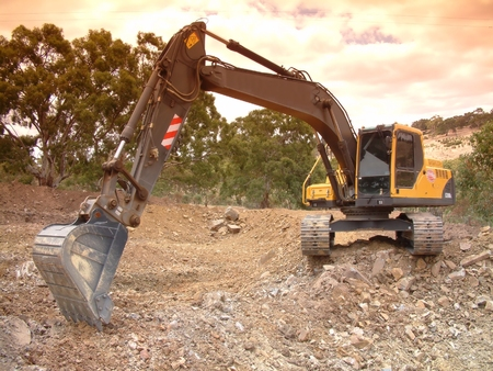 earth moving: Skidsteer Excavator at work moving and digging dirt with soil earth works construction in new housing development subdivision.  Earth mover bucket excavation landscaping dam and large hole filling