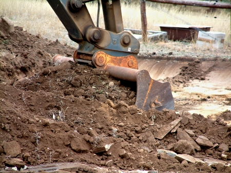 earth moving: Excavator at work moving and digging dirt with soil earth works construction in new housing development subdivision.  Earth mover bucket excavation landscaping dam and large hole filling Stock Photo