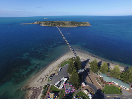 granite park: Aerial view of Granite Island and Causeway Jetty at Victor Harbor Harbour South Australia Tourism Holiday Area, featuring historic horse drawn carriage cart and calm water blue bay scenes