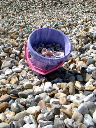 pebles: Bucket full of sea shells Stock Photo