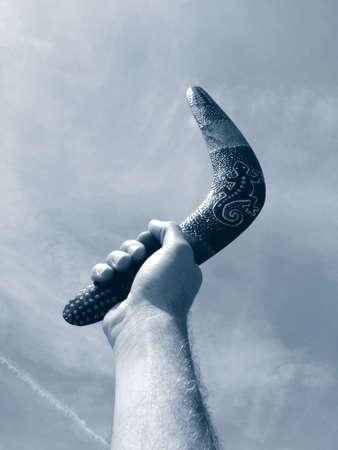 Hand holding a boomerang photo