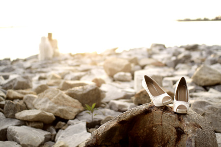 Wedding couple in rocky beach with wedding shoe on the foreground