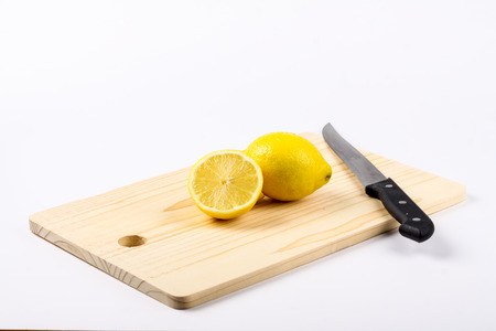 bodyparts: lemon cut with kitchen knife isolated in white