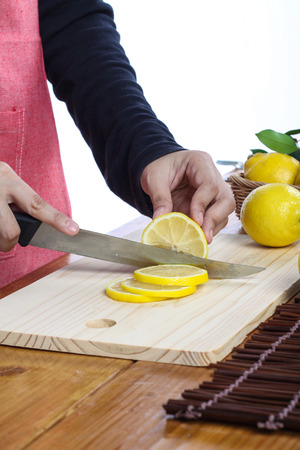 bodyparts: woman cutting lemon in clean environment Stock Photo