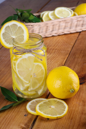 bodyparts: lemonade with some fresh uncut yellow lemon in wooden kitchen table Stock Photo