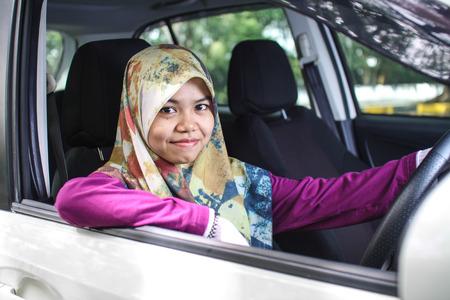 potrait: potrait of muslim woman driving her car