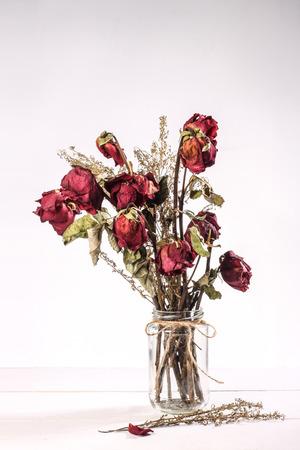 Boeket van rode droge rozen in glazen vaas op een witte achtergrond Stockfoto